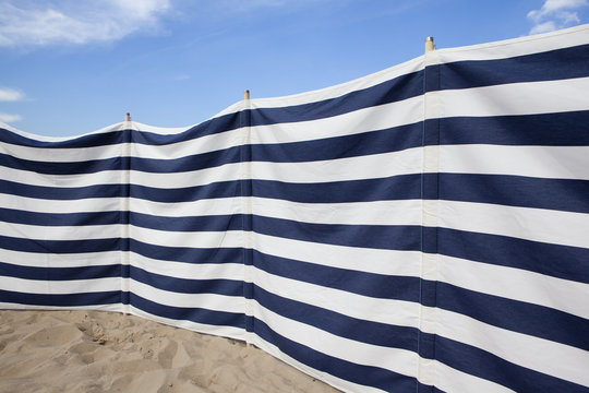 blue and white striped windbreak at the beach