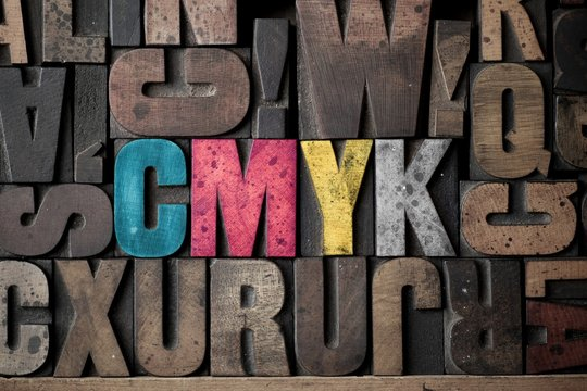 The letters 'CMYK' spelled out in very old letterpress blocks.