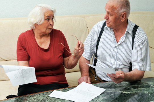 Senior couple reading documents at home
