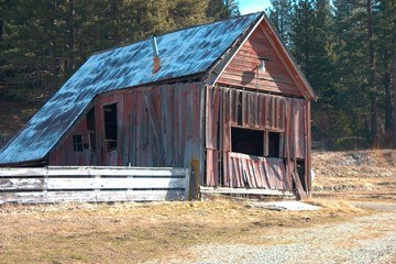 Rustic Red Barn in Mountain Pasture Side View