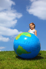 Girl stands on grass and looks aside next to an inflatable globe