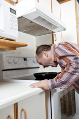 Man with anger management issues yelling at frying pan