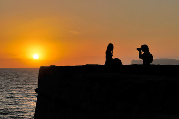 Photographer and model at sunset in Alghero, Sardinia, Italy