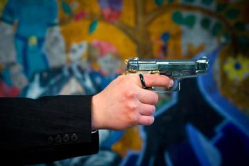 the gun pistol in hand, on graffiti background.