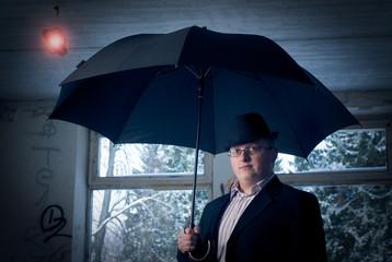 man with umbrella in old building. Conceptual idea theme