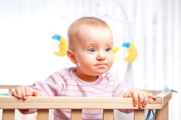 Baby im Laufstall schaut ernst und konzentriert