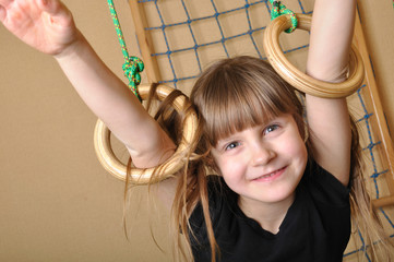 child playing at gymnastic rings