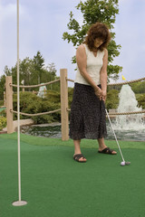 Woman enjoying a round of mini golf