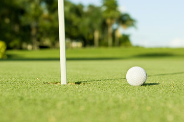Golf ball on putting green beside hole