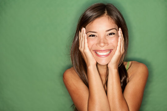 Surprised happy woman on green background