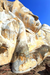 giant reclining buddha face statue over blue sky
