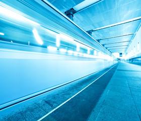 blue underground platform with moving train