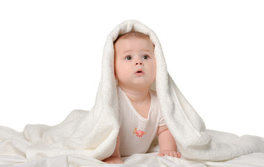 The baby under a towel. Age of 8 months. It is isolated on a whi