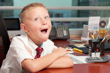 Cute young boy in a business office with funny expression