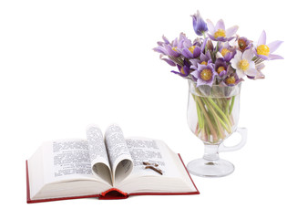 Pages of a bible curved into a heart shape. Bunch of flowers