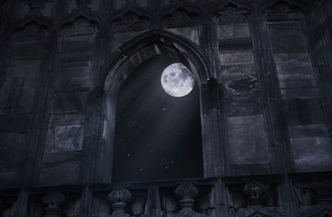 Full moon seen through the window of the old castle