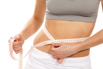 Athletic fit slim female measuring her waist