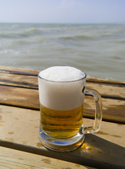 Mug of fresh beer on the wooden pier