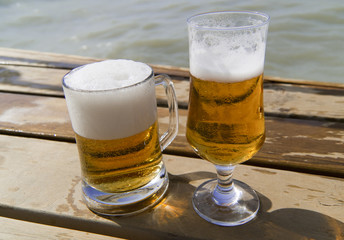 Mug and bocal of  beer on the wooden pier