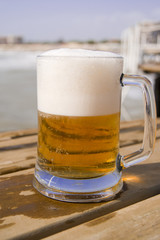 Mug of beer on the wooden pier