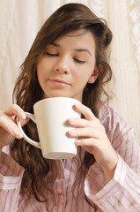 Mädchen mit Kaffeebecher im Bett