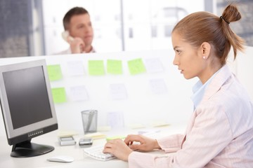 Young woman busy in office using computer