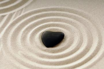 Stein als schwarzes Herz im Sand mit Spuren