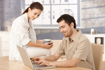 Young couple browsing internet at home smiling