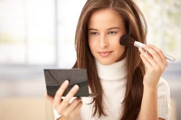 Attractive woman applying makeup
