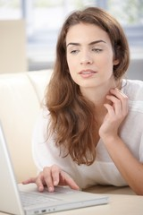 Young woman using laptop laying on sofa