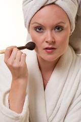 Beautiful blonde thirties caucasian woman doing makeup