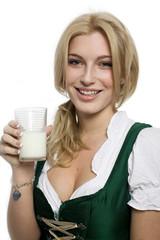 Mädchen im Dirndl hält ein Glas Milch in der Hand
