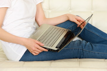 young women on white couch relaxing and using laptop computer