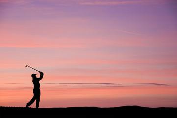 Golfer silhouette against stunning sunset sky