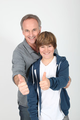 Father and son standing with thumbs up