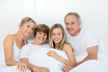 Portrait of happy family in bed in the morning
