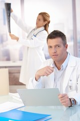 Male doctor sitting at desk doing paperwork