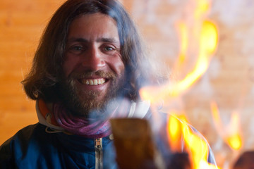 A man with long hair near a fire