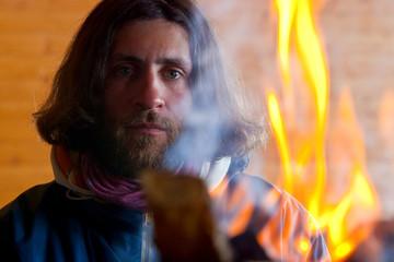A man with long hair near a fire