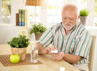 Elderly man taking pill at home