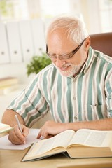 White hair pensioner writing letter at home
