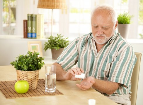 Elderly man taking pill at home