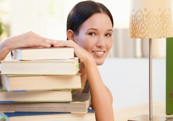 Cheerful young woman posing with books
