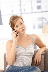 Attractive woman talking on mobile at home