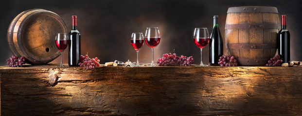 still life with red wine with barrel on old wood