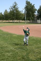 Boy in baseball uniform playing catch