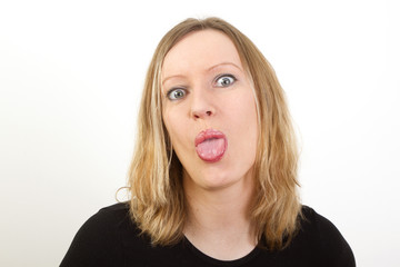 Portrait of young blond woman showing tongue