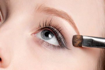 Beautiful young adult woman applying cosmetic brush