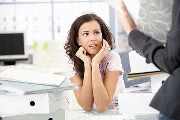 Young secretary sitting shocked in office