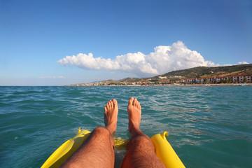 men's feet on yellow inflatable mattress, sea, far shore